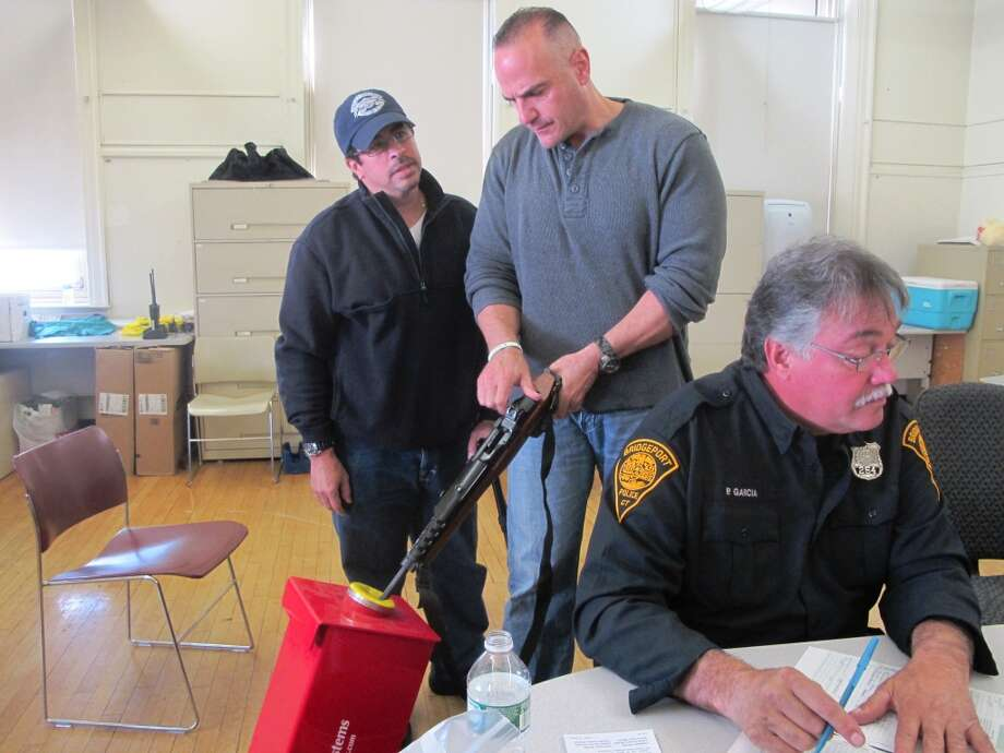 Bridgeport police inspect a gun that was turned at a buyback event Saturday in the city's East End. Dozens of guns were surrendered in exchange for cash or grocery vouchers. Photo: Wes Duplantier, Connecticut Post