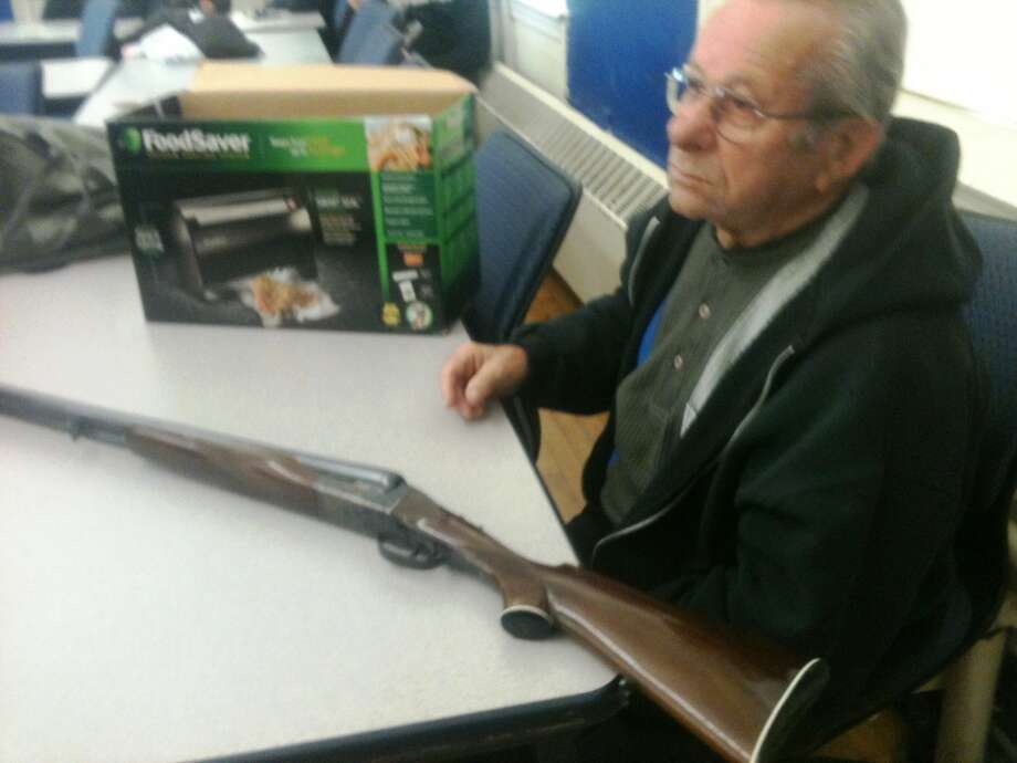 Bridgeport resident Umberto Lisi turned in a 42-year-old Spanish-made hunting rifle at Saturday's event. He said he used to use it for hunting but that he doesn't hunt anymore. Photo: Wes Duplantier, Connecticut Post