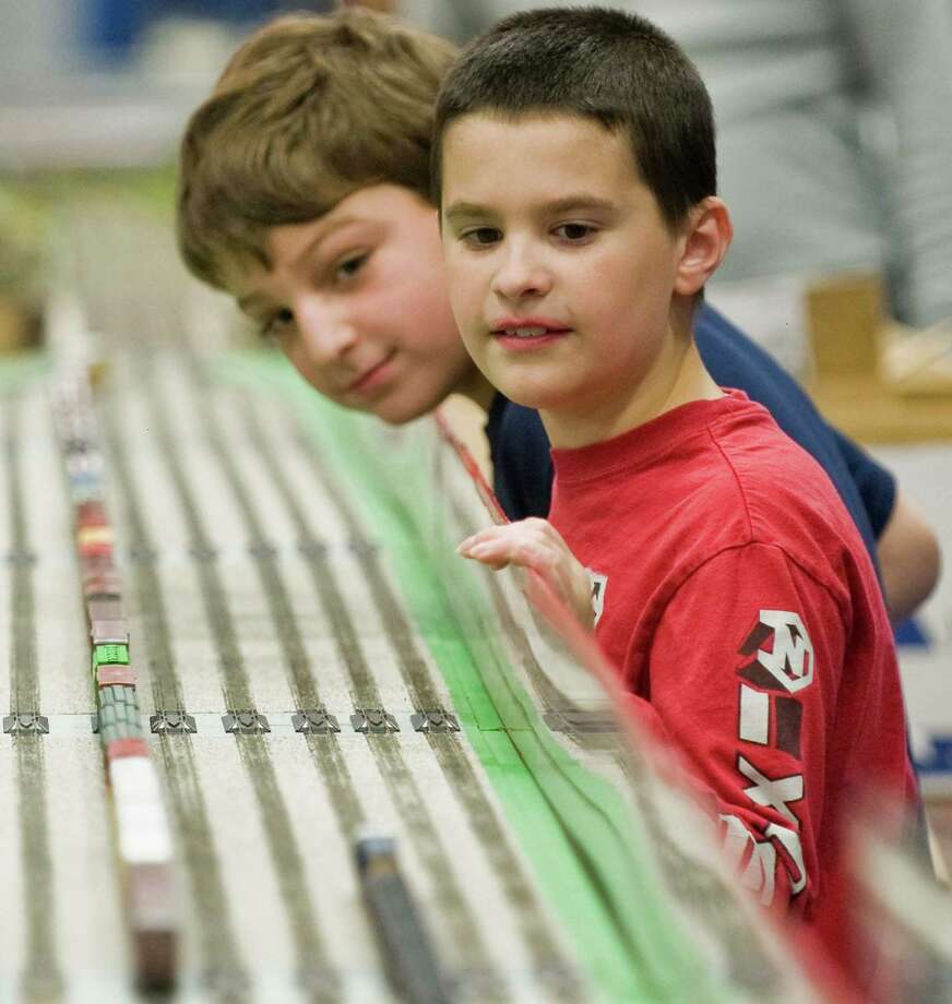 John Pellegino, 10, left, and Daniel Gregory, 11, wait for the trains to come around on this display at Greenberg's Train & Toy Show held at the O'Neill Center. Saturday, Nov. 16, 2013 Photo: Scott Mullin / The News-Times Freelance