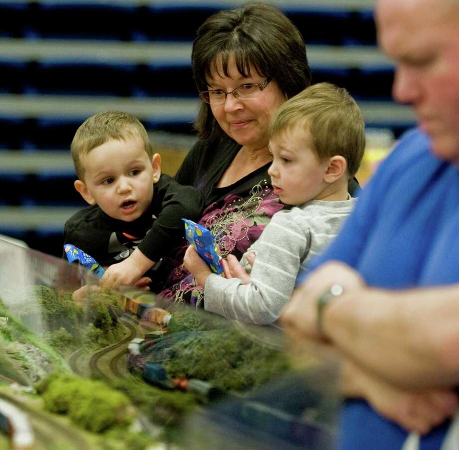 Parker Mckirryher, left, and Paddy Long, both 3, held by their grandmother Teri Archer, watch the trains in motion at Greenberg's Train & Toy Show held at the O'Neill Center. Saturday, Nov. 16, 2013 Photo: Scott Mullin / The News-Times Freelance