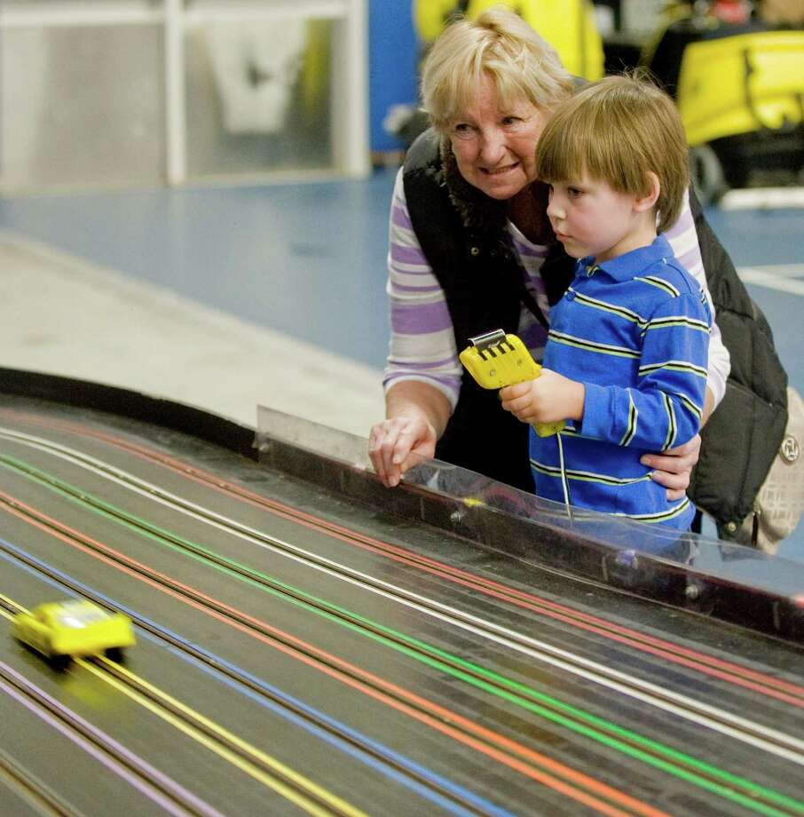 Eileen Sweet, great grandmother to Kevin W. Markey, 3, work a slot car at Greenberg's Train & Toy Show held at the O'Neill Center. Saturday, Nov. 16, 2013 Photo: Scott Mullin / The News-Times Freelance
