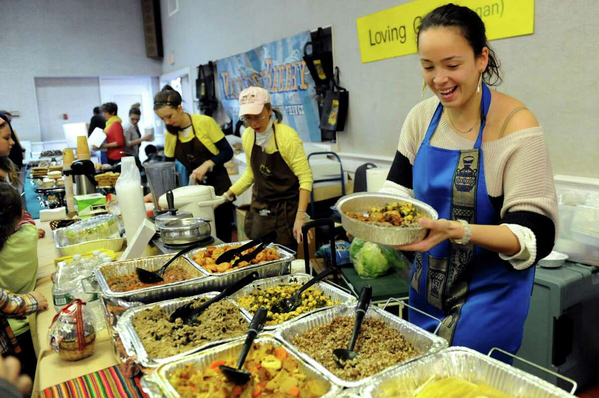 Andrea Lloyd, owner of La Empanada Llama in Albany, right, fills a dish with vegetarian delights during Albany VegFest 2013 on Saturday, Nov. 16, 2013, at the Polish Community Center in Albany, N.Y. The annual event, presented by the Albany Vegan Network, featured vendors, speakers, cooking demonstrations and food samplings. (Cindy Schultz / Times Union)