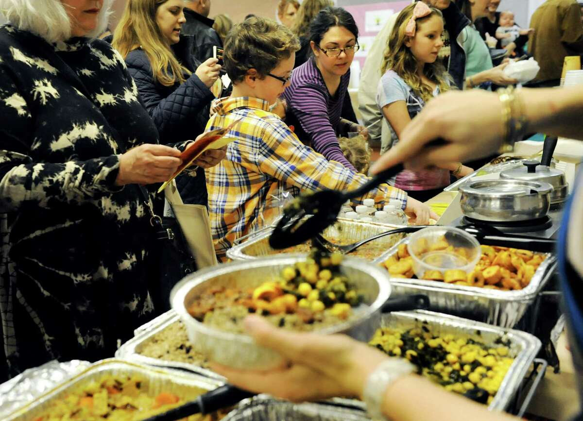 Festival goers choose vegetarian delights during Albany VegFest 2013 on Saturday, Nov. 16, 2013, at the Polish Community Center in Albany, N.Y. The annual event, presented by the Albany Vegan Network, featured vendors, speakers, cooking demonstrations and food samplings. (Cindy Schultz / Times Union)