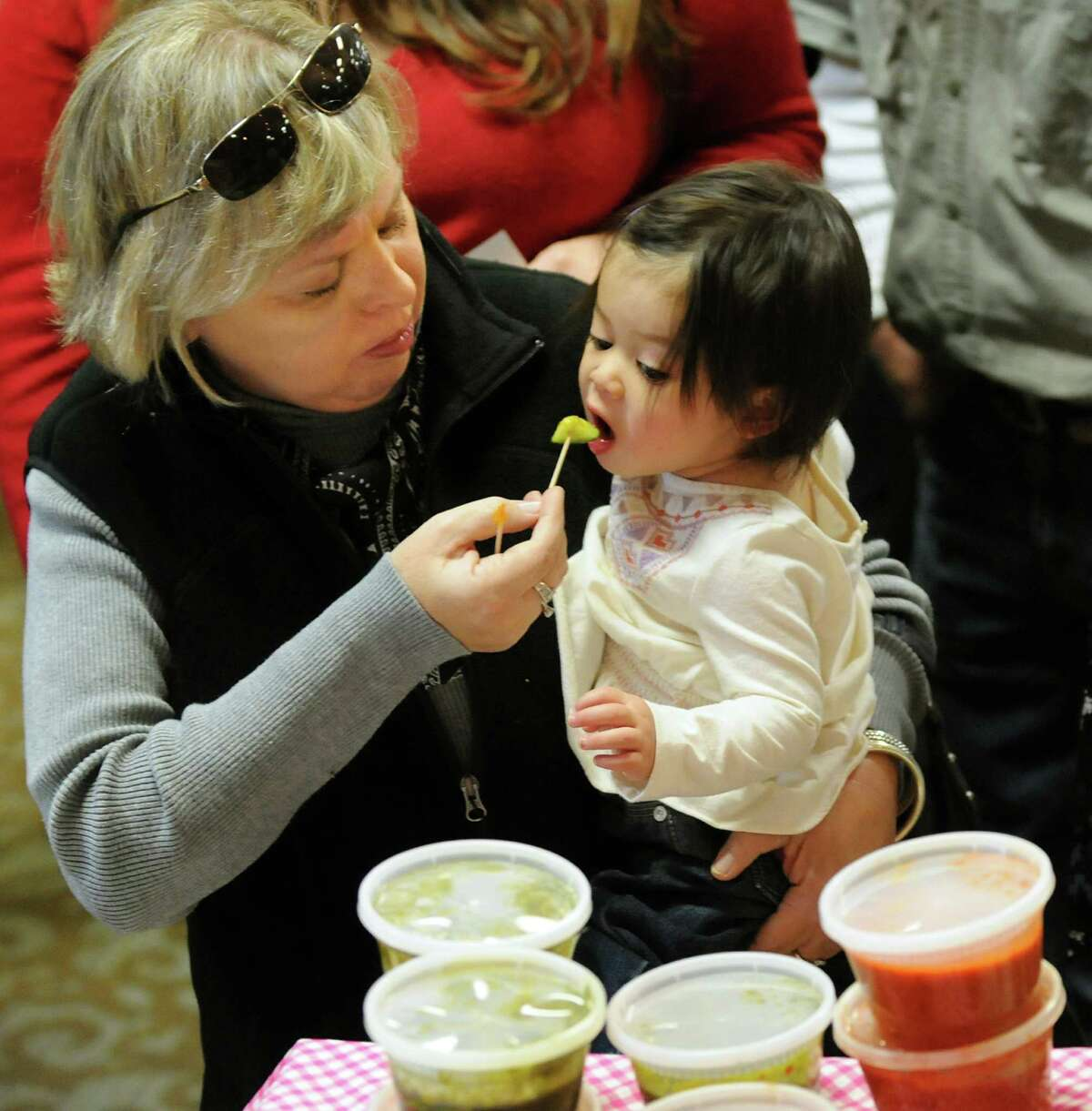Janet Shaye of Slingerlands, left, gives her granddaughter Enilia Eng, 1, a food sampling during Albany VegFest 2013 on Saturday, Nov. 16, 2013, at the Polish Community Center in Albany, N.Y. The annual event, presented by the Albany Vegan Network, featured vendors, speakers, cooking demonstrations and food samplings. (Cindy Schultz / Times Union)