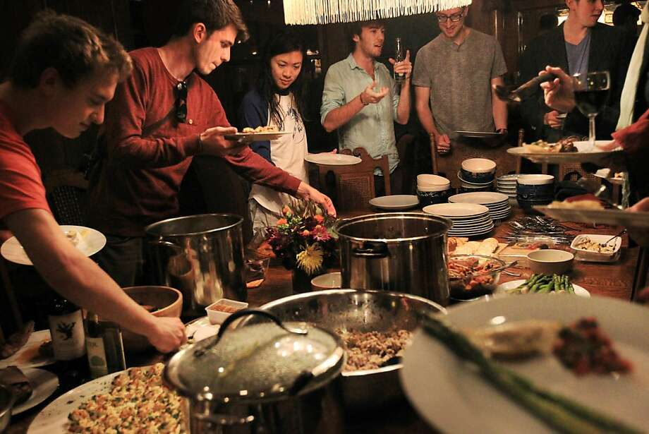 Sunday dinner at the Embassy is a potluck for residents and guests. Visitors Lucas Didier (left), Vinicius Depizzol, Stephanie Sara Chong, Adrien Montcoudiol, Tom Bielecki and Jon Lipinski dish up their meals. Photo: Leah Millis, The Chronicle