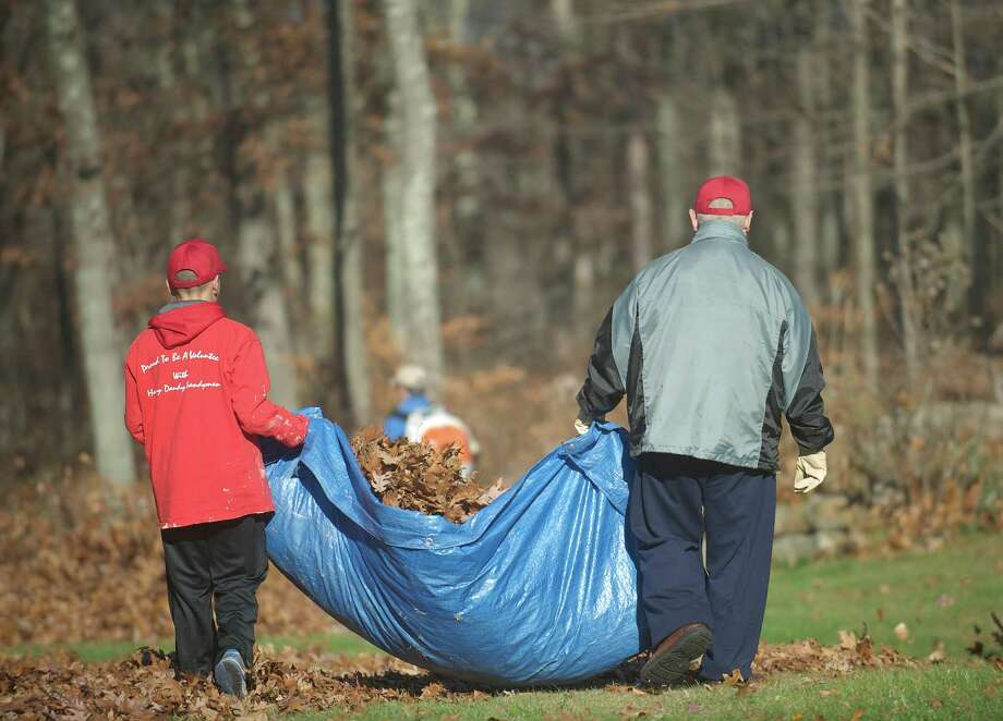 Christopher Tapia , 13, of New Milford, and Joe Casalone, of Bethel, carry a tarp full of leaves during the annual Rake n Bake in Brookfield, Conn, on Saturday November 16, 2013. Photo: H John Voorhees III / The News-Times Freelance