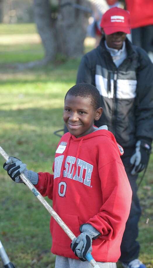 Teddy Mbuthi, 14, of Lowell, MA, works in a yard on Brookfield Meadows during the annual Rake n Bake in Brookfield, Conn, on Saturday November 16, 2013. Mbuthi came to volunteer with a friend. Photo: H John Voorhees III / The News-Times Freelance