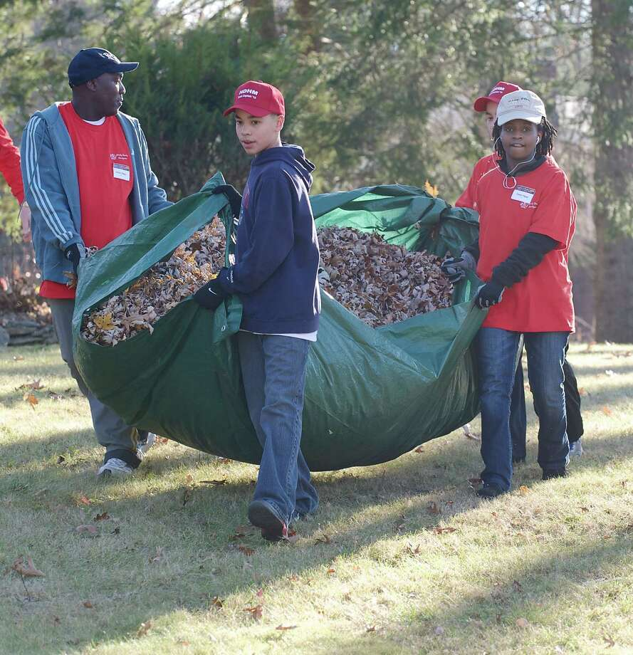 Simon Ngugi, left, from Lowell, MA, helps carry a tarp full of leaves with Joseph Tapia, 13, of New Milford, and his niece Evelyn Ngugi, 21, as part of the annual Rake n Bake in Brookfield, on Saturday November 16, 2013. They are working in a yard on Brookfield Meadows, Brookfield, Conn. Photo: H John Voorhees III / The News-Times Freelance