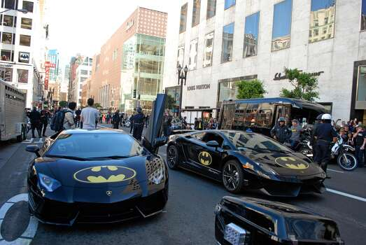 The Lamborghini Batmobiles wait for Batkid and the Caped Cursader's entourage to finish their lunch at Burger Bar outside of Union Square. The Make-A-Wish foundation, SF officials and thousands of volunteers came together to transform San Francisco into Gotham City to grant 5-year-old Leukemia survivor Miles Scott his wish of being Batkid on Friday, Nov. 15, 2013. Photo: Sara Gobets, Special To The Chronicle