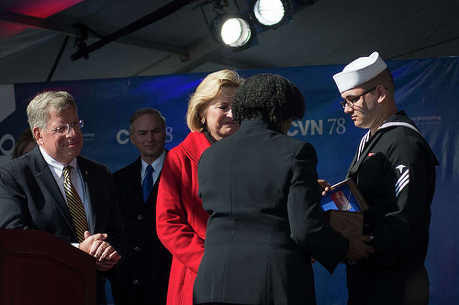 Navy Navy Hospitalman Timothy McBride McBridem, right, of Ravena receives a ceremonial box that contains the broken sparkling wine bottle Susan Ford Bales, third from left, used to christen the new USS Gerald R. Ford.