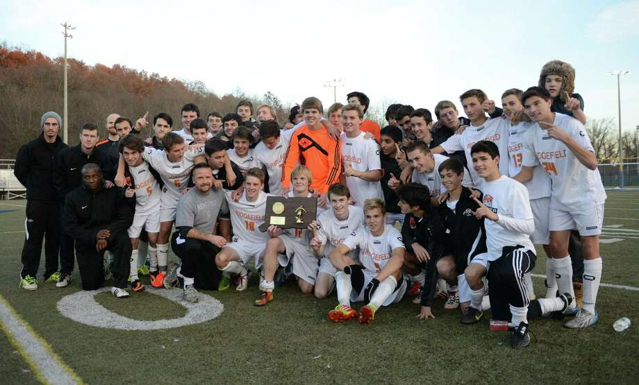 Ridgefield hoists the championship trophy after its 1-1 tie with Glastonbury in the CIAC Class LL high school boys soccer championship game at Municipal Stadium in Waterbury, Conn. on Saturday, Nov. 16, 2013. Photo: Tyler Sizemore / The News-Times