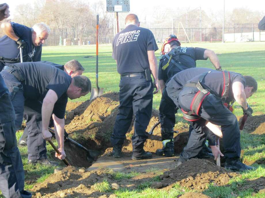 A team effort resulted in the successful rescue of a German shepard/basset hound mix that wandered into a concrete drainage pipe at Fairfled Warde field on Saturday, Nov. 16, 2013. Photo: Wes Duplantier, Connecticut Post / Connecticut Post