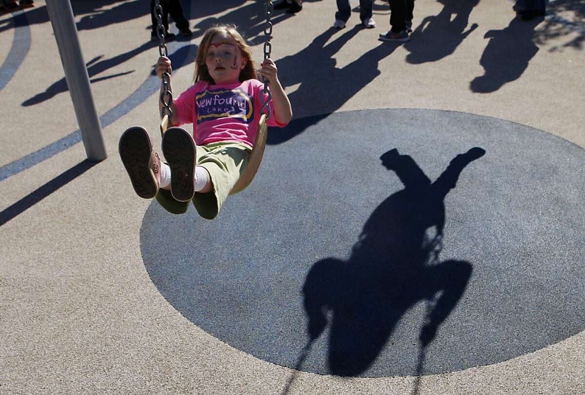 Samantha Wiley swings on the playground as the shadow of another child swinging is seen on the ground during the reopening of Palega park in San Francisco, Calif. on Saturday, Nov. 16, 2013.
