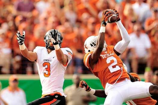 Texas safety Mykkele Thompson intercepts a pass against Oklahoma State. Photo: Stacy Revere, Getty Images