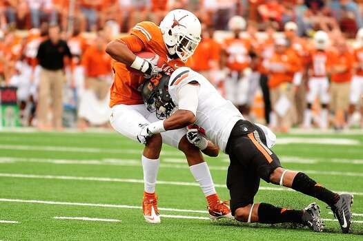 Mike Davis of Texas is tackled by Caleb Lavey of Oklahoma State. Photo: Stacy Revere, Getty Images
