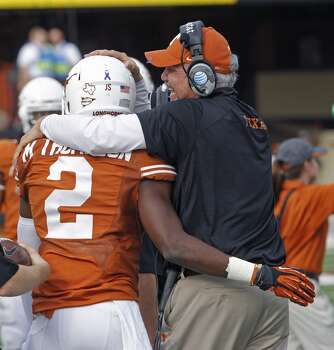 Texas assistant coach Duane Akina celebrates an interception by safety Mykkele Thompson. Photo: Michael Thomas, Associated Press