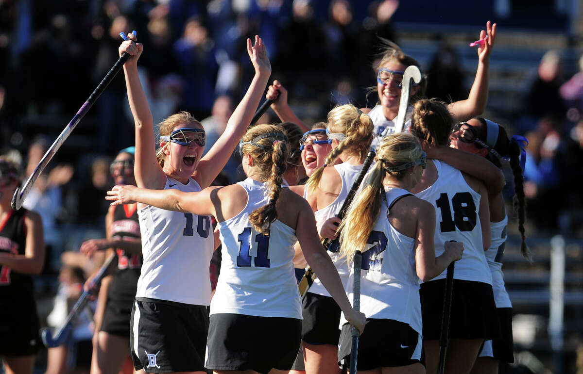 Darien teammates surround Hollis Perticone after she scored on a penatly shot, during Class L girls state field hockey championship action against Cheshire in Wethersfield, Conn. on Saturday March 16, 2013.