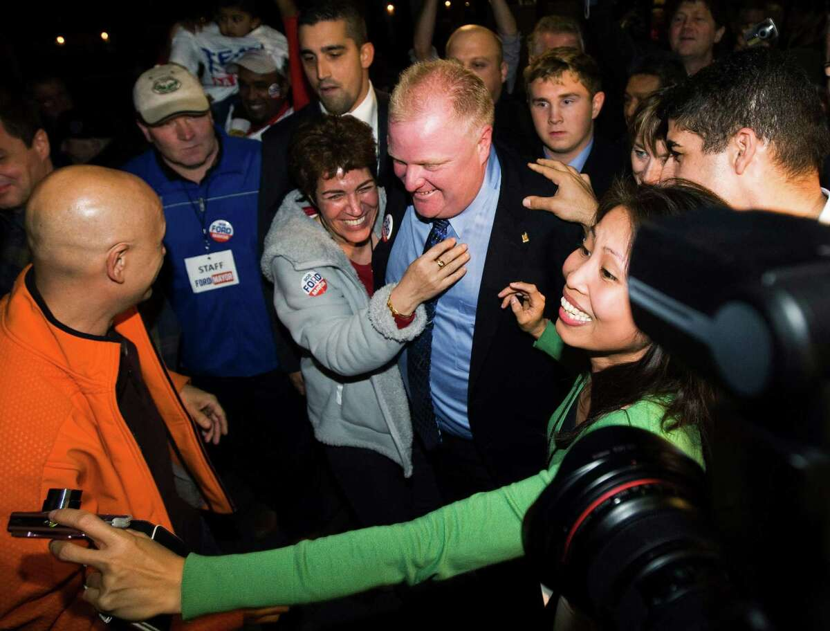 In this Monday, Oct. 25, 2010 photo, Toronto Mayor-elect Rob Ford, center, is greeted by a mob of supporters as he arrives to speak to supporters in Toronto. When he was elected, Ford's bluster and checkered past were widely known. A plurality of voters backed him anyway, eager to shake things up at a City Hall they viewed as elitist and wasteful. (AP Photo/The Canadian Press, Nathan Denette)