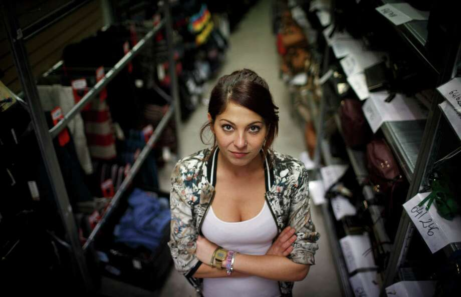 Melissa Abadia, who moved from Spain to Amsterdam to find employment three years ago, stands in the stock room of River Island where she now works. Youth unemployment has reached staggering levels. Photo: ILVY NJIOKIKTJIEN, STR / NYTNS