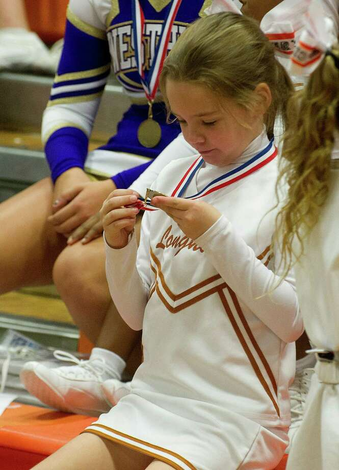 Longhorns cheerleaders look at their medals during the Stamford Youth Foundation Cheerleading exhibition show at Stamford High School on Saturday, November 16, 2013. Photo: Lindsay Perry / Stamford Advocate