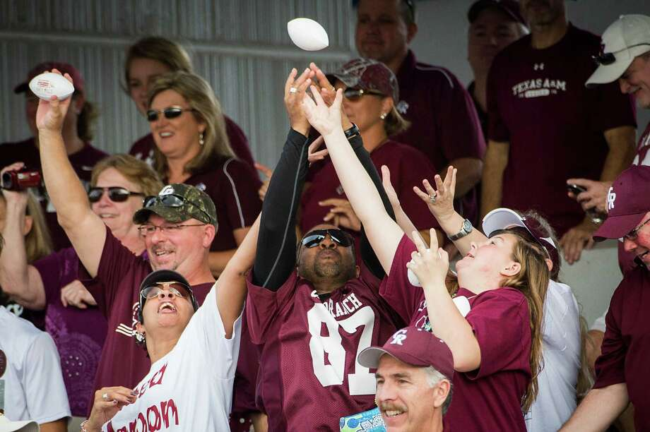 Cinco Ranch fans reach for footballs thrown into the crowd by cheerleaders during a high school football playoff game against Bellaire at Barnett Stadium Saturday, Nov. 16, 2013, in Houston. Photo: Smiley N. Pool, Houston Chronicle / © 2013  Houston Chronicle
