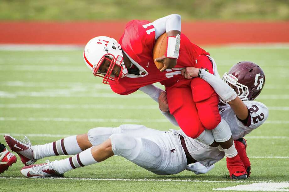 Bellaire quarterback Trevon Smith (11) is tackled by Cinco Ranch safety Trent Soechting (22) during a high school football playoff game at Barnett Stadium Saturday, Nov. 16, 2013, in Houston. Photo: Smiley N. Pool, Houston Chronicle / © 2013  Houston Chronicle