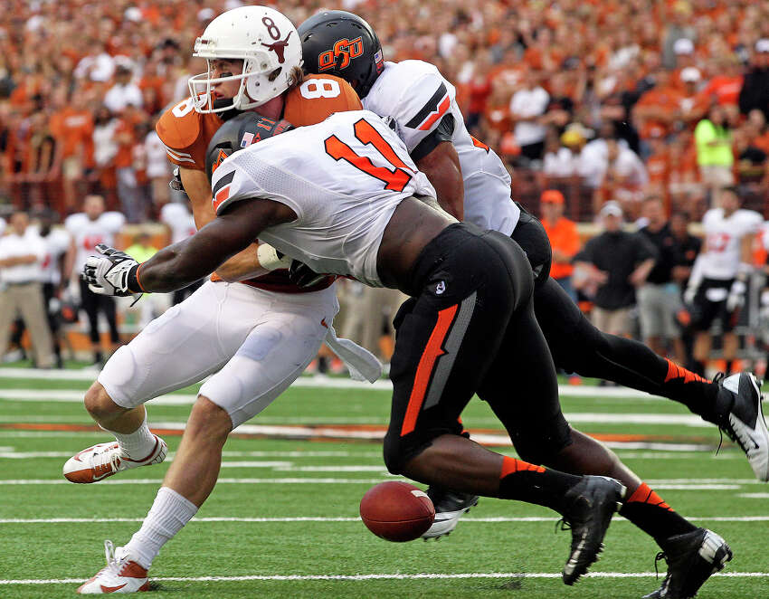 Longhorn receiver Jordan Shipley is crunched between defenders as he tries to make a catch as Texas plays Oklahoma State at Darrell K. Royal Stadium in Austin on November 16, 2013.