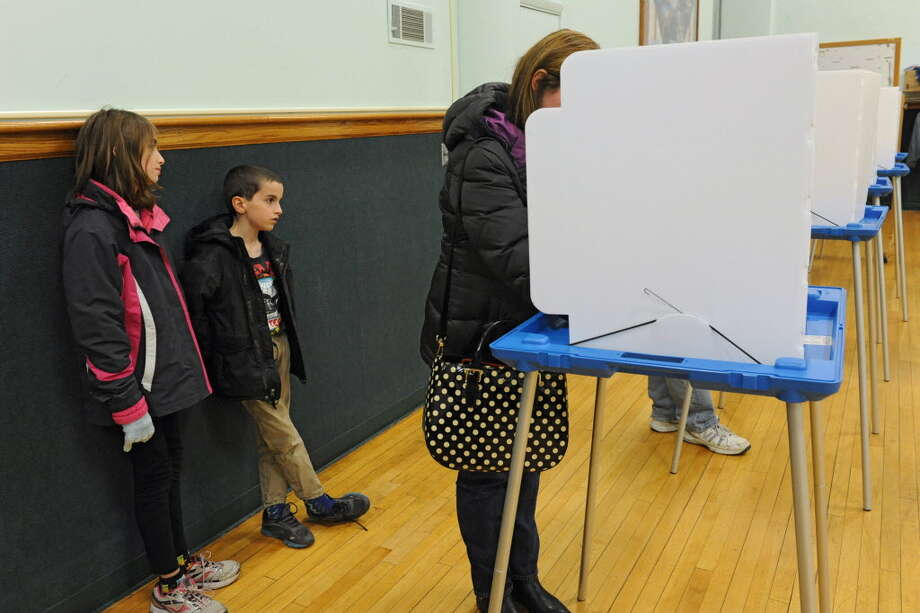 Carol Roeder of Delmar votes while her two children Gillian, 11, left, and Griffin, 9, wait at Bethlehem Town Hall on Nov. 5. Nine days later, voters in Guilderland were asked to vote again. (Lori Van Buren / Times Union)