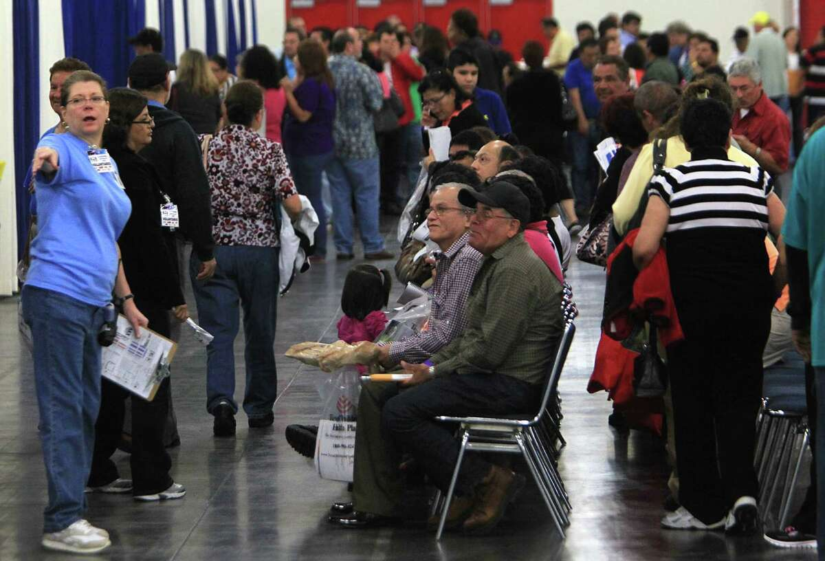Volunteers guide people through various healthcare enrollment and information booths during the Affordable Care Act town hall meeting at George R. Brown Convention Center.