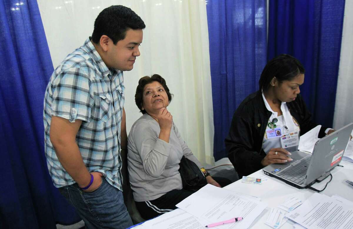 Juana Galvan looks at son Eduardo Galvan to translate information being given by guide Dolontria Bryant as Mrs. Galvan attempts to enroll for insurance after the Affordable Care Act town hall meeting at George R. Brown Convention Center.