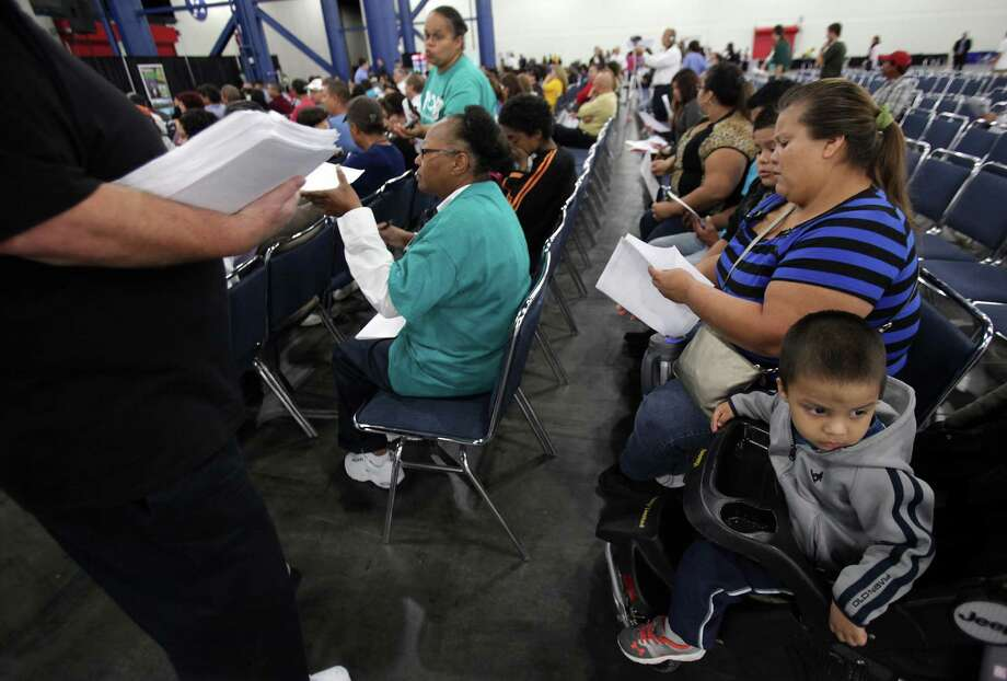 Luz Maria Coronado receives medical insurance information as her son Silviano Coronado, 2, quietly sits with his family during an Affordable Care Act town hall meeting. The Coronado Family attended meeting to receive information about how to enroll a family of six for healthcare. Photo: Mayra Beltran, Houston Chronicle / © 2013 Houston Chronicle
