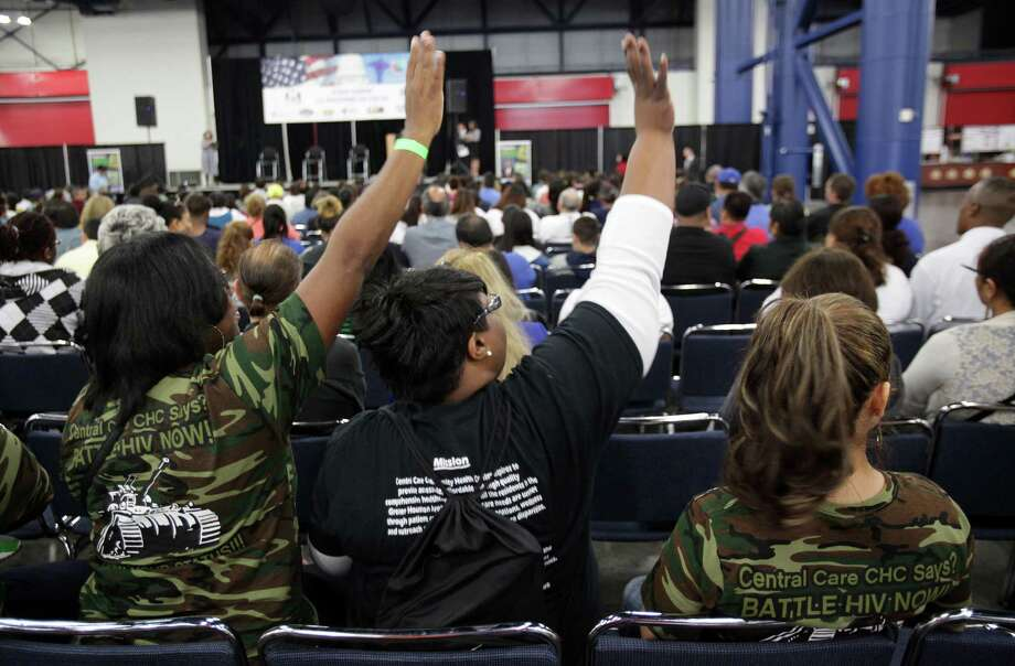 Volunteers with Central Care Community Health Care wave down team members as they get ready to listen to the Affordable Care Act town hall meeting at George R. Brown Convention Center. Photo: Mayra Beltran, Houston Chronicle / © 2013 Houston Chronicle