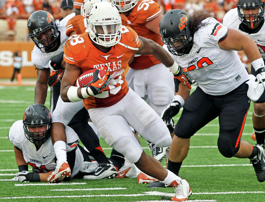 Malcolm Brown cuts through the middle to get a second quarter touchdown as Texas plays Oklahoma State at Darrell K. Royal Stadium in Austin on November 16, 2013. Photo: TOM REEL