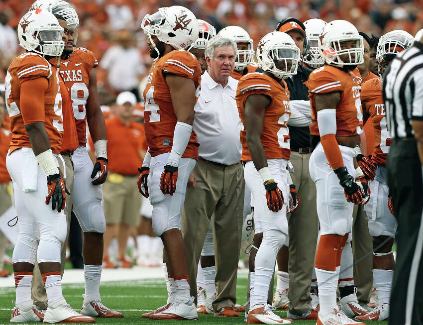 Coach Mack Brown stares away from the huddle as UT falls behind as Texas plays Oklahoma State at Darrell K. Royal Stadium in Austin on November 16, 2013.