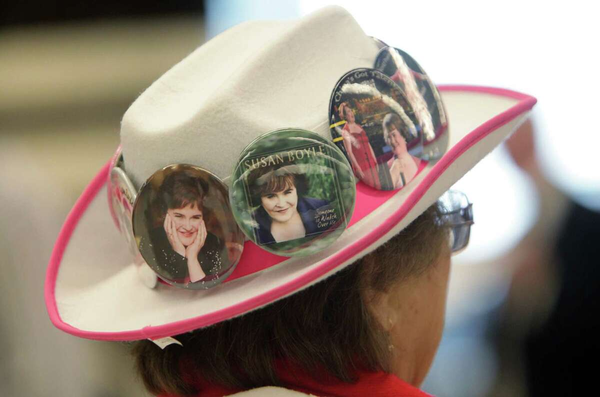 Grace Roone, 75, wears Britain's Got Talent star singer Susan Boyle buttons on her cowboy hat as fan club members wait to welcome Boyle at Bush Intercontinental Airport on Saturday, Nov. 16, 2013, in Houston. Boyle will perform two concerts at Lakewood Church Sunday.
