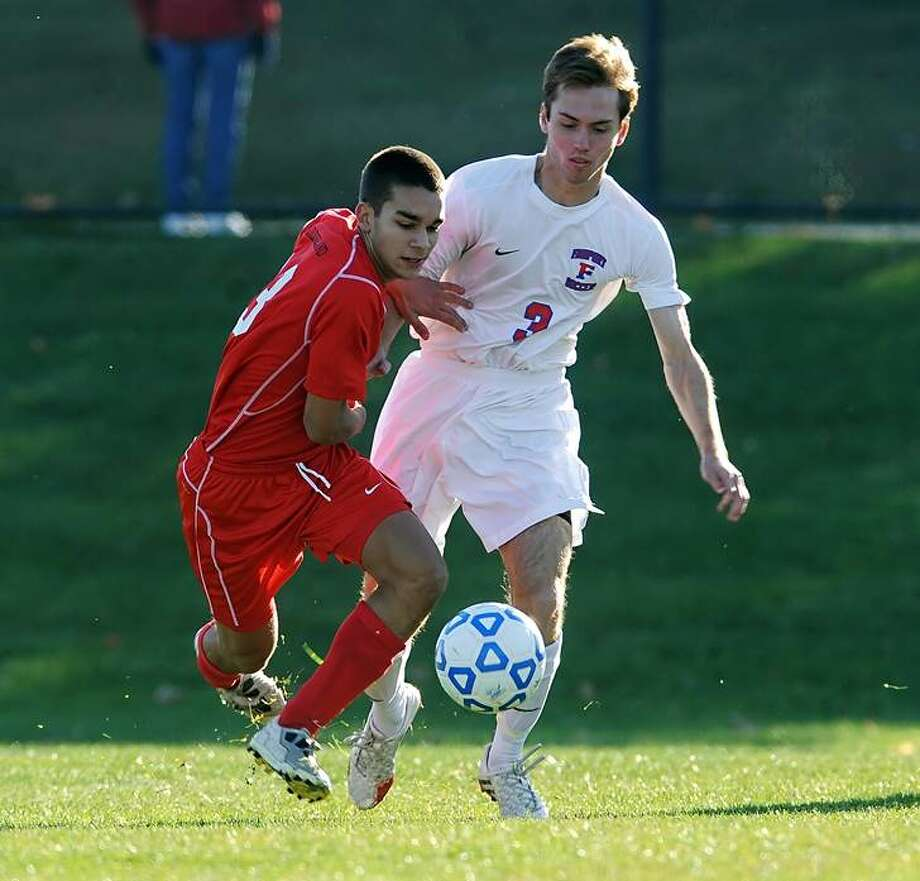 Guilderland's Daniel Dibiase, left, battles for the ball against Fairport's Alex Mangerian in a Class AA state semifinal at Middletown High School on Saturday, Nov. 16, 2013. Fairport advances to the Class AA final after beating Guilderland, 3-1.  (Adrian Kraus / Special to the Times Union)
