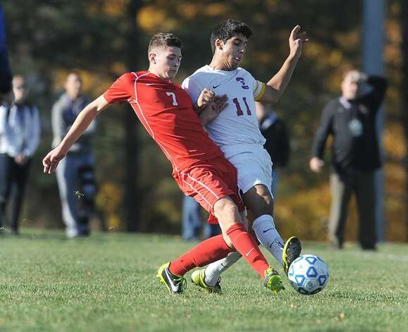 Fairport's Rani Hubeishy, right, and Guilderland's Keagan Ciaschetti reach for the ball in a Class AA state semifinal at Middletown High School on Saturday, Nov. 16, 2013. Fairport advances to the Class AA final after beating Guilderland, 3-1.  (Adrian Kraus / Special to the Times Union)