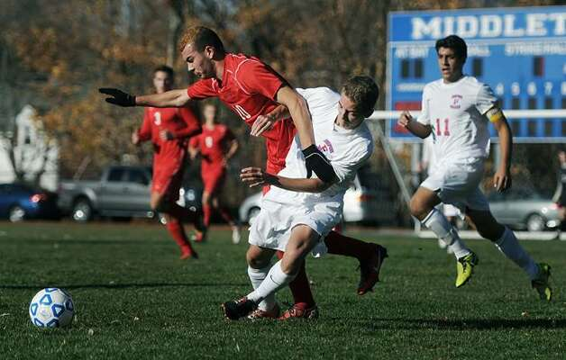 Guilderland's Kledis Capollari, left, wins the ball from Fairport's Nick Christidis in a Class AA state semifinal at Middletown High School on Saturday, Nov. 16, 2013. Fairport advances to the Class AA final after beating Guilderland, 3-1.  (Adrian Kraus / Special to the Times Union)