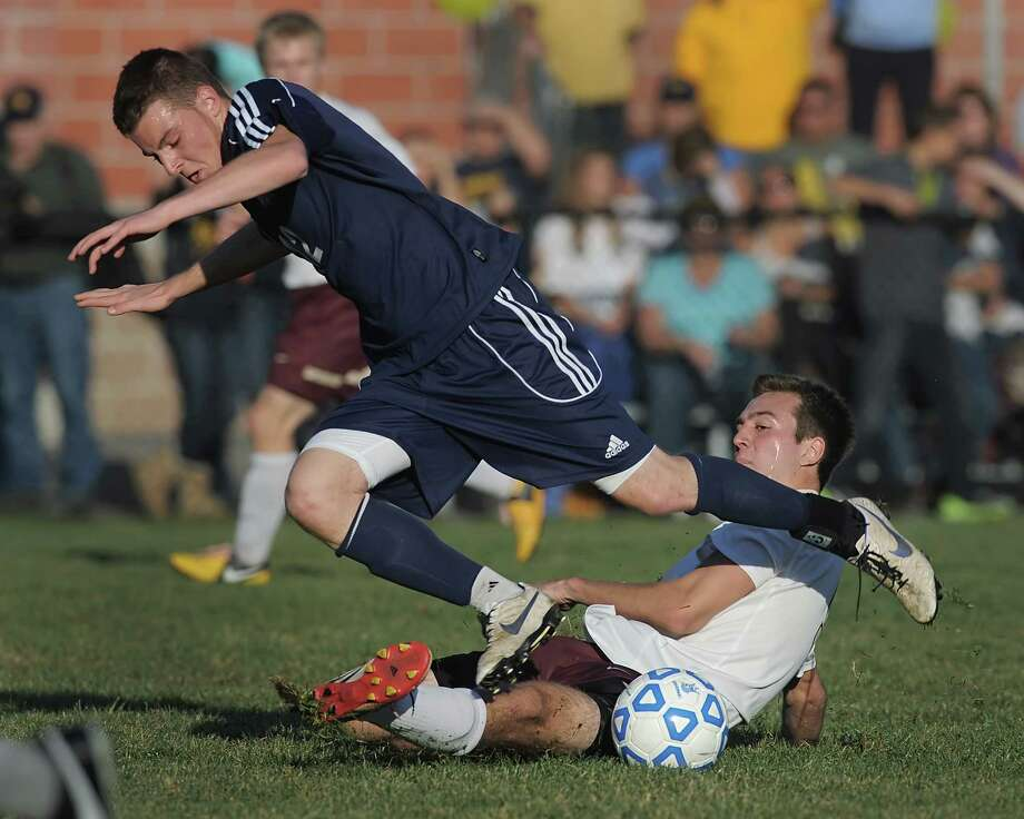 Averill Park's Owen Nuss, left, loses the ball on a slide tackle by Pittsford Mendon's John Vangellow in a Class A semifinal at the 2013 NYSPHSAA Boys Soccer Championships held at Middletown High School on Saturday, November 16, 2013.  Averill Park was eliminated by Pittsford Mendon-V after a 2-0 loss.  (Adrian Kraus / Special to the Times Union) Photo: Adrian Kraus / © akoPhoto 2011