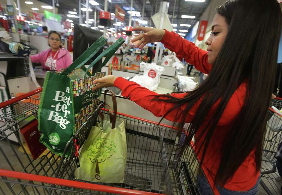 Justine Torres handles plenty of both kinds of bags at the San Antonio H-E-B where she works as a cashier. Photo: BOB OWEN, Staff / © 2012 San Antonio Express-News