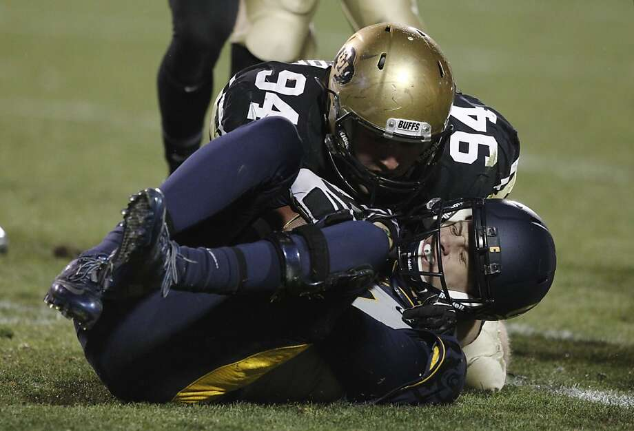 Quarterback Jared Goff, tackled by Colorado's Tyler Henington, struggled before being pulled and after returning. Photo: David Zalubowski, Associated Press