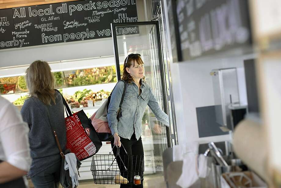 Shannon Thomas, above, grabs an item from the dairy case while shopping at the new Local Mission Market in S.F.'s Mission District. Photo: Michael Short, The Chronicle