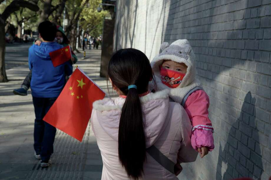 Visitors to the Forbidden City carry children holding Chinese flags in Beijing on Saturday. On Friday, China significantly eases the country's strict one-child policy for the first time in three decades. Photo: Ng Han Guan, STF / AP