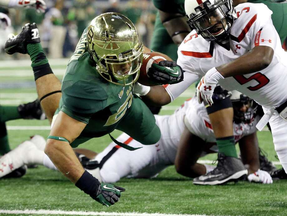 Baylor running back Devin Chafin, left, dives in for a touchdown against Texas Tech defensive back Tre' Porter (5) during the first half of an NCAA college football game in Arlington, Texas, Saturday, Nov. 16, 2013. (AP Photo/LM Otero) Photo: LM Otero, Associated Press / AP