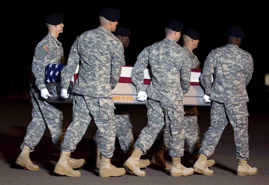 An Army carry team, carries the transfer case containing the remains of Army Staff Sgt. Richard L. Vazquez of Seguin, Texas, upon arrival at Dover Air Force Base, Del. on Saturday, Nov. 16,  2013. The Department of Defense announced the death of Vazquez who was supporting Operation Enduring Freedom in Afghanistan. ( AP Photo/Jose Luis Magana) Photo: Jose Luis Magana, Associated Press / FR159526 AP