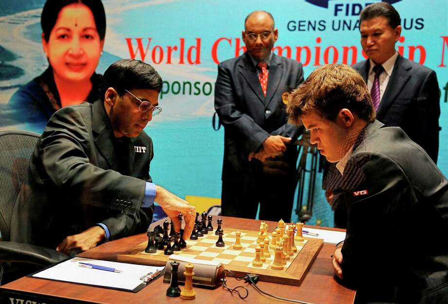 Defending champion India's Viswanathan Anand, left, makes a move Saturday against Norway's Magnus Carlsen during the first game of the World Chess Championship in Chennai, India. Carlsen is seen as having an edge in the best- of-12 series. Photo: STR / AP
