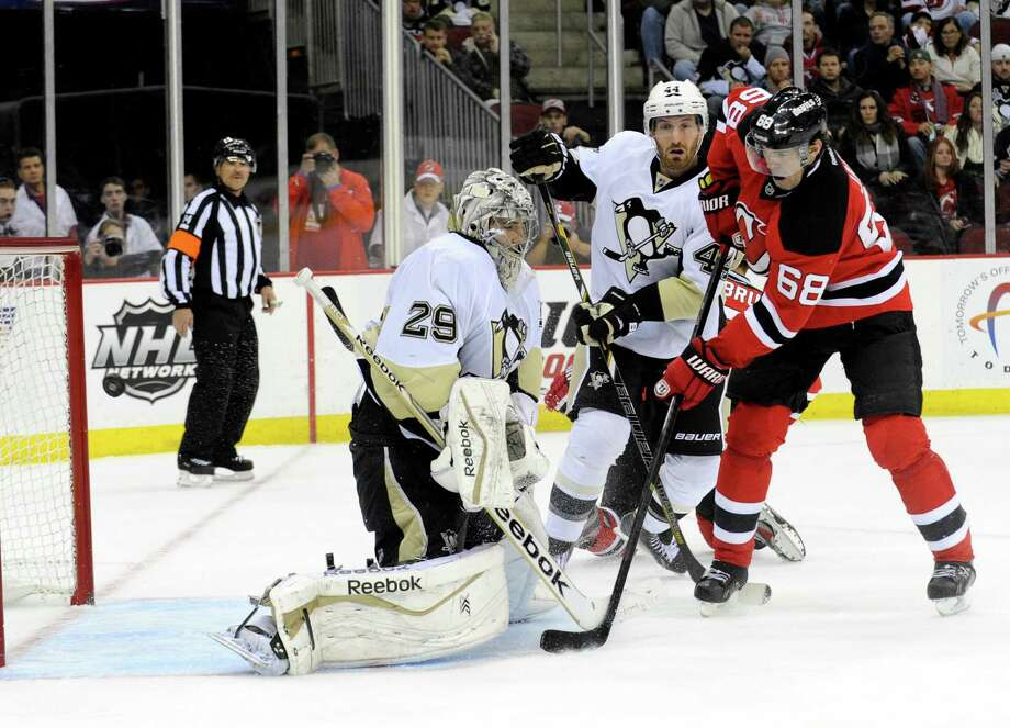 New Jersey Devils' Jaromir Jagr (68), of Czech Republic, watches the puck go into the net past Pittsburgh Penguins goaltender Marc-Andre Fleury, left, for a goal by Devils' Adam Larsson during the second period of an NHL hockey game Saturday, Nov. 16, 2013, in Newark, N.J. (AP Photo/Bill Kostroun) ORG XMIT: NJBK104 Photo: Bill Kostroun / FR51951 AP