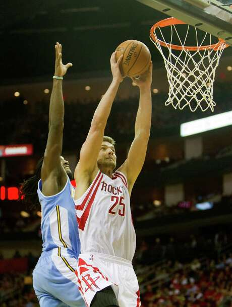 Nuggets forward Kenneth Faried, left, comes up short on his attempt to block the dunk of Rockets forward Chandler Parsons, who had 20 points. Photo: Cody Duty, Staff / © 2013 Houston Chronicle