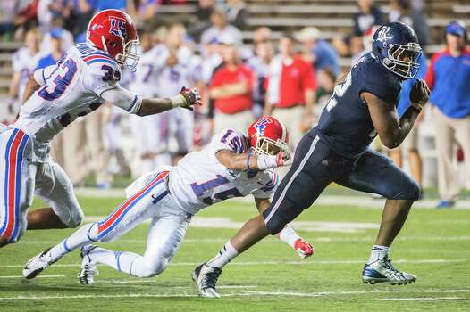 Rice's Charles Ross leaves Louisiana Tech's Thomas McDonald, left, and Bryson Abraham behind on a 19-yard touchdown run that was the fifth of the game for the Owls running back Saturday night. Photo: Smiley N. Pool, Staff / © 2013  Houston Chronicle