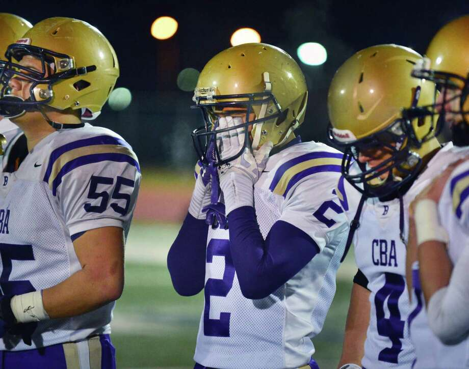CBA's #2 Jason Micelli, center, hides his face as they lose the Class AA regional semifinal against Monroe-Woodbury Saturday Nov. 16, 2013, at Dietz Stadium Kingston, NY.  (John Carl D'Annibale / Times Union) Photo: John Carl D'Annibale / 00024620A